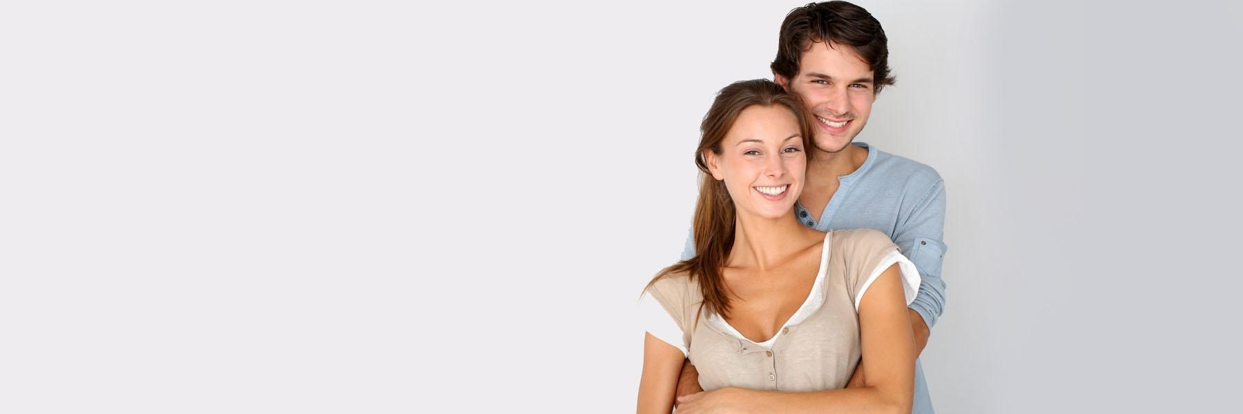 Young couple hugging & smiling l Porcelain Veneers Doylestown PA