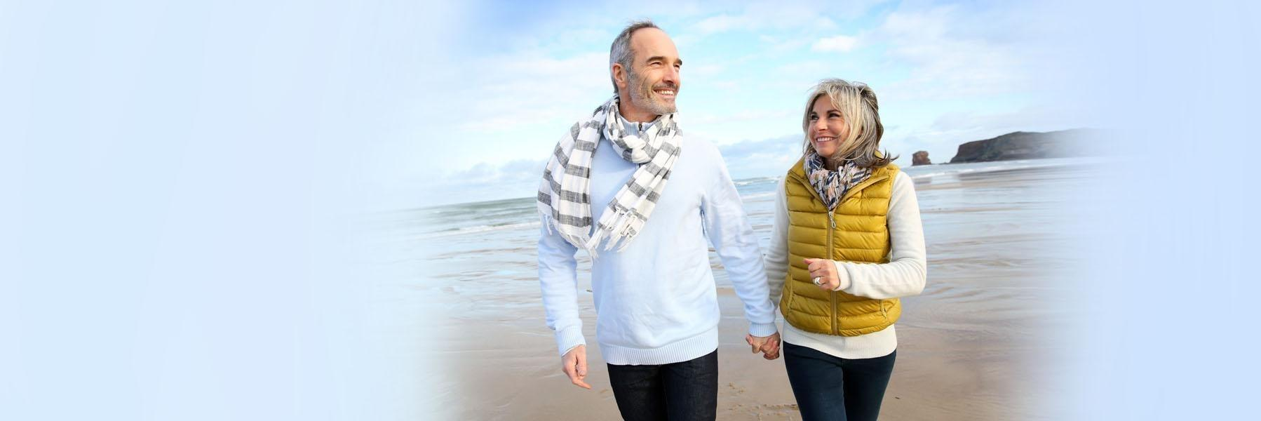 Older couple walking on beach l Dental Implants Doylestown PA