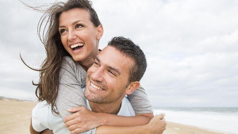 man giving woman a piggyback ride | cosmetic dentist doylestown pa
