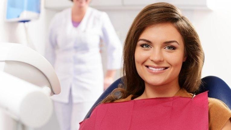 woman smiling in dentist chair | Veneers in Doylestown PA