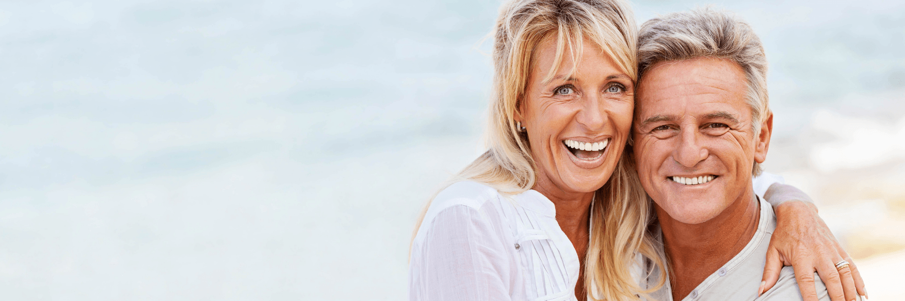 Older couple smiling on a beach l Dental Bridges Doylestown Dental Group